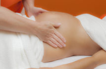 Pregnant young latina woman with beautiful skin, being wrapped with a towel, lying on a bed and having a relaxing prenatal massage, various techniques, glamour clarity effect